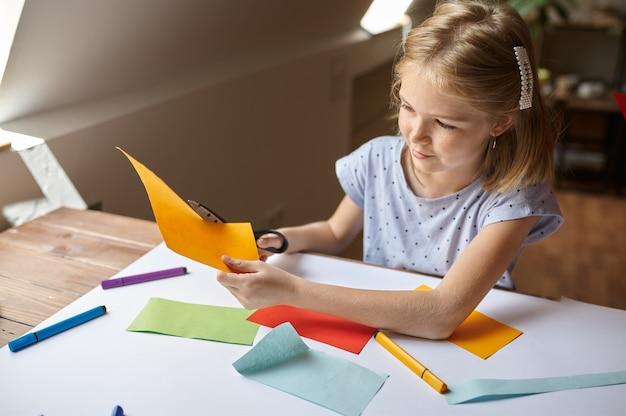 Маленькая девочка режет цветную бумагу, ребенок в мастерской
