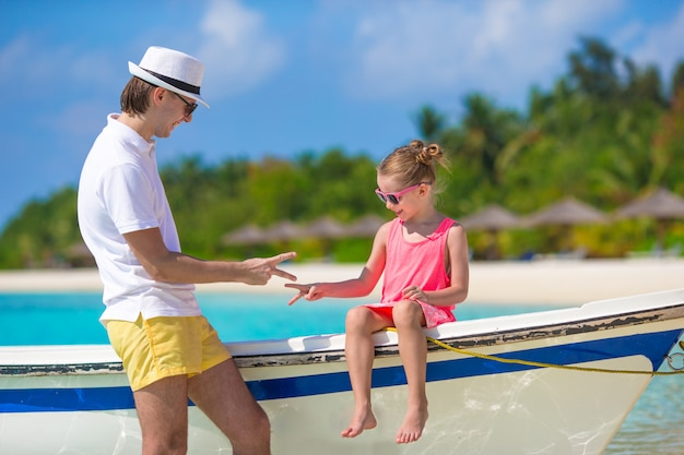 Little girl and dad on boat during tropical beach vacation