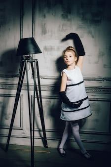 빈티지 드레스에 작은 소녀 댄스. 우아한 매력적인 드레스와 장갑에 아이입니다. 복고풍 소녀, 패션 모델, 아름다움, 플로어 램프. 패션과 뷰티, 핀업 스타일, 어린 시절.
