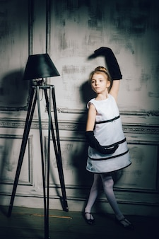 Little girl dance in a vintage dress. child in an elegant glamorous dress and gloves. retro girl, fashion model, beauty, floor lamp. fashion and beauty, pinup style, childhood.