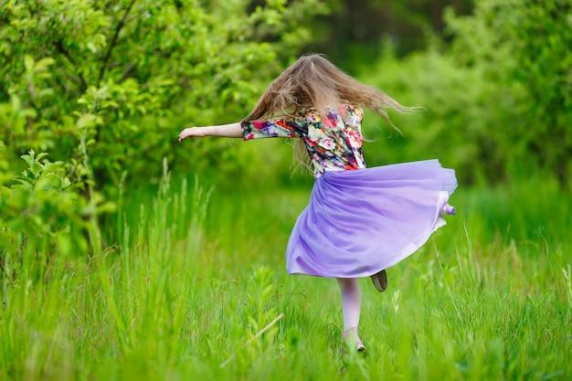 Маленькая девочка танцует на открытом воздухе