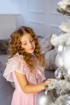 Маленькая девочка украшает рождественское дерево, новогоднюю концепцию. малыш возле елки, девушка в розовом платье.