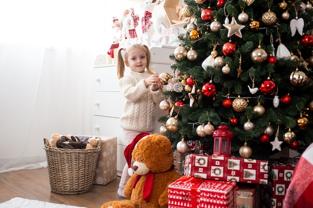 Little girl decorates christmas tree at home