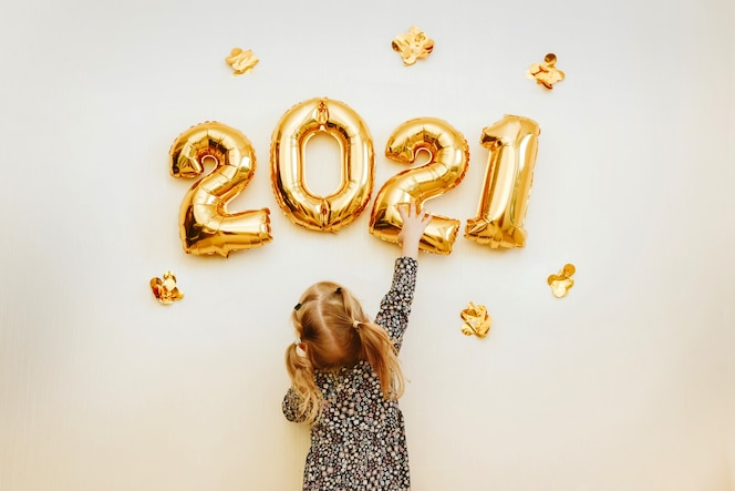 Little girl decorates the wall of the house with golden numbers