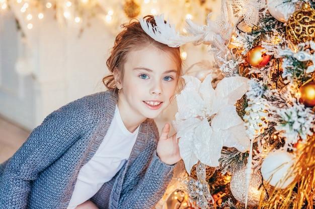Маленькая девочка украшает елку дома