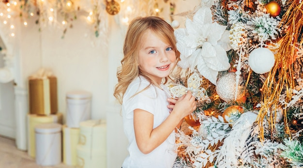 Little girl decorating christmas tree on christmas eve at home. young kid in light room with winter decoration. time for celebration concept banner
