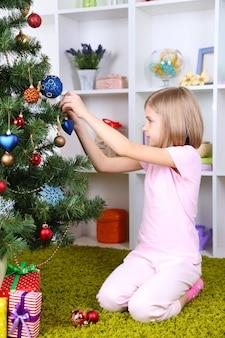 部屋のクリスマスツリーを飾る少女