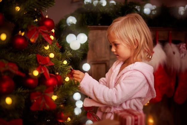 Bambina che decora un albero di natale