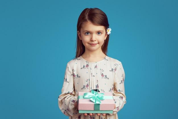 Маленькая девочка демонстрирует упакованную подарочную коробку с лентой на синей стене