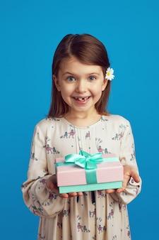 Маленькая девочка демонстрирует упакованную подарочную коробку с лентой на синей стене Premium Фотографии