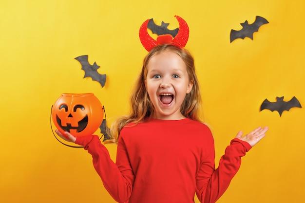 Little girl in a devil costume holds a bucket of pumpkin