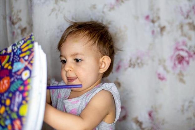 Маленькая девочка старательно рисует в альбоме цветными маркерами уроки с детьми дома и в школе.