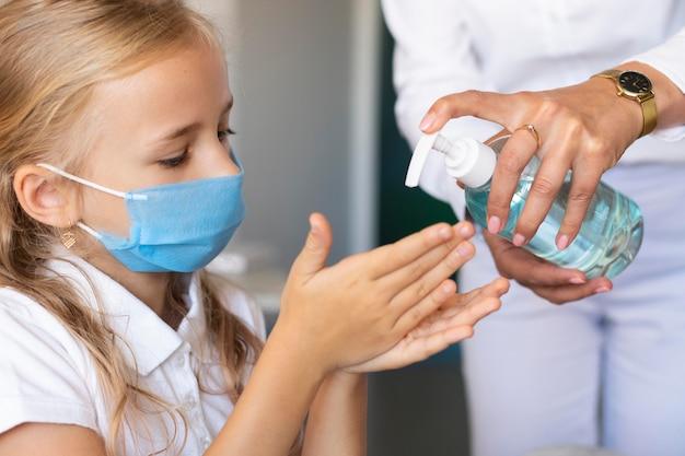 Bambina che disinfetta le sue mani