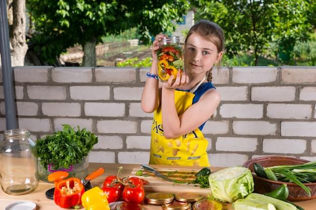 さいの目に切ったばかりの新鮮な野菜のボトルを表示し、目の前にある野菜の品揃えから瓶に入れている少女