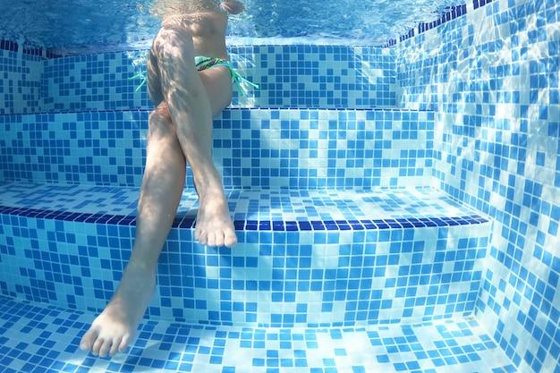 Маленькая девочка ныряет в воду, летние каникулы.