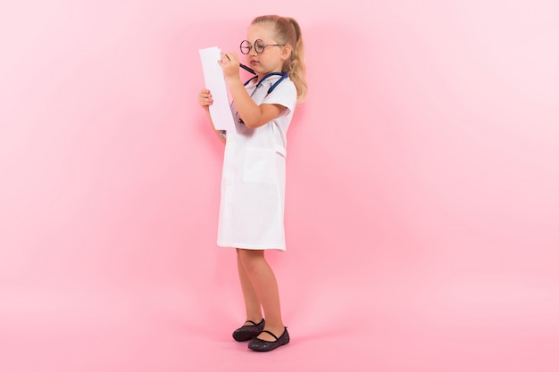 Little girl in doctor costume with paper
