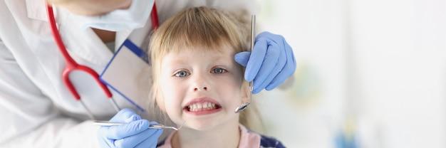 Маленькая девочка врач стоматолог проводит осмотр ротовой полости