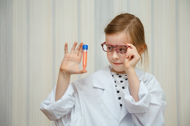 Little girl in a doctor s smock examines test tubes with tests.