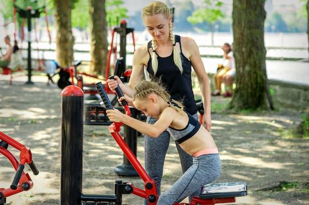 Маленькая девочка делает упражнения на тренажере под руководством тренера молодой женщины в парке