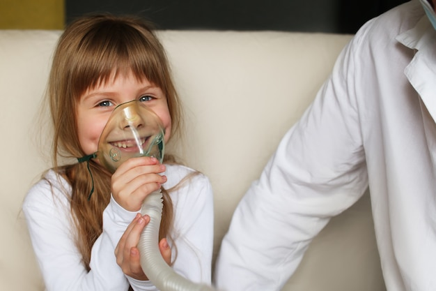 A little girl does inhalation with a spray at home, a doctor is nearby. inhaler for children from asthma inhalation nebulizer steam sick cough concept.