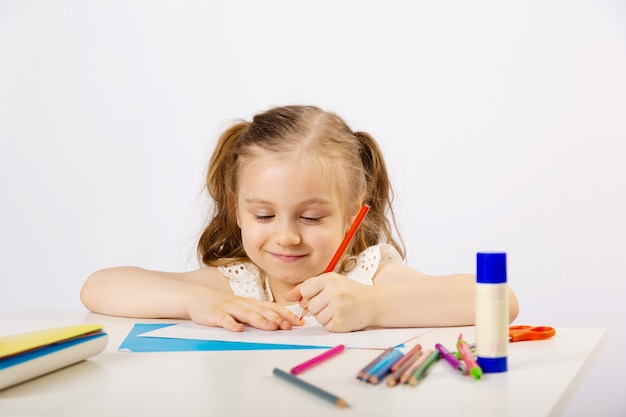 Little girl does lessons, draws, smiles