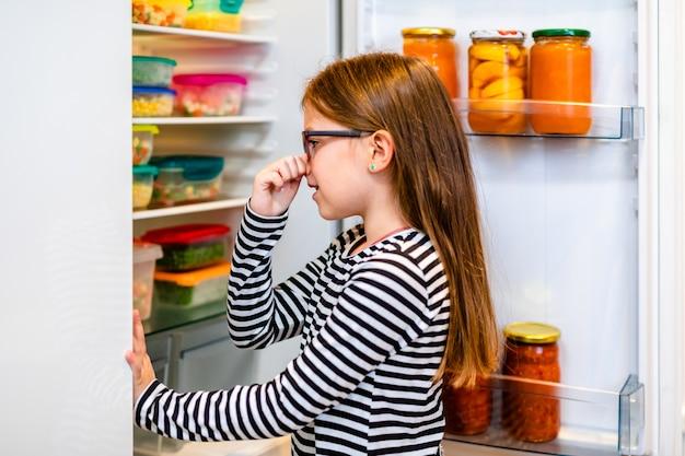Маленькая девочка не любит запах овощей из холодильника.