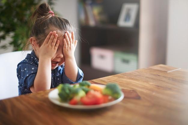 어린 소녀는 야채를 먹고 싶지 않다