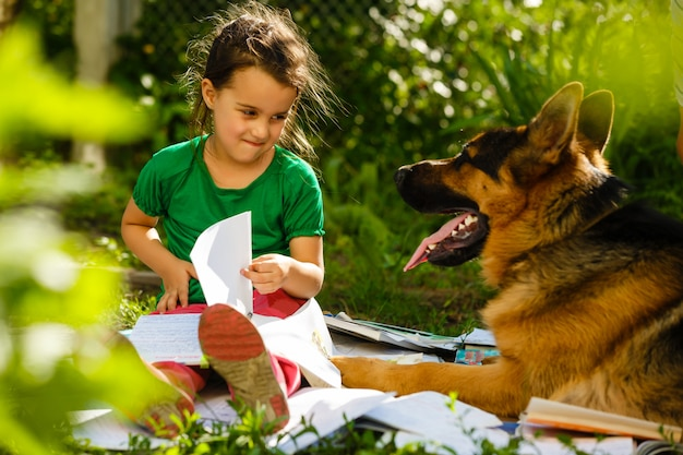Little girl and dog studying