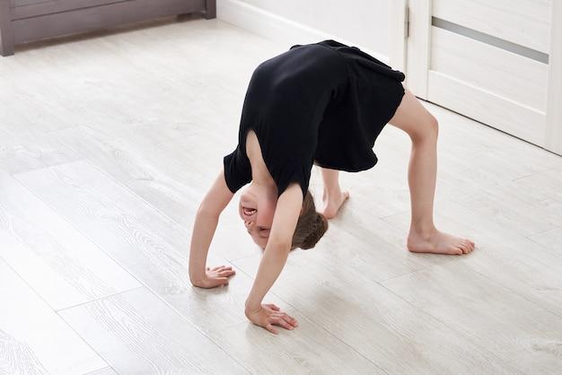 Маленькая девочка делает упражнения гимнастики на дому