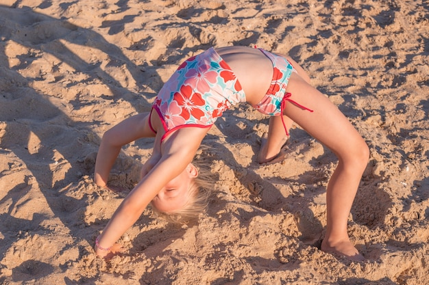 Little girl doing exercise bridge on the sand. summer vacation at sea, tourism and sports.