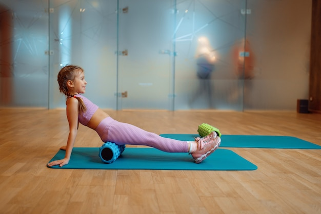 Маленькая девочка делает упражнения с массажным роликом на циновке в тренажерном зале, фитнес-тренировки. девушка в спортивной одежде, ребенок на тренировке в спортивном клубе