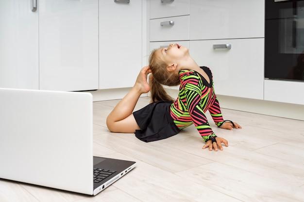 オンラインで自宅で体操をしている少女。