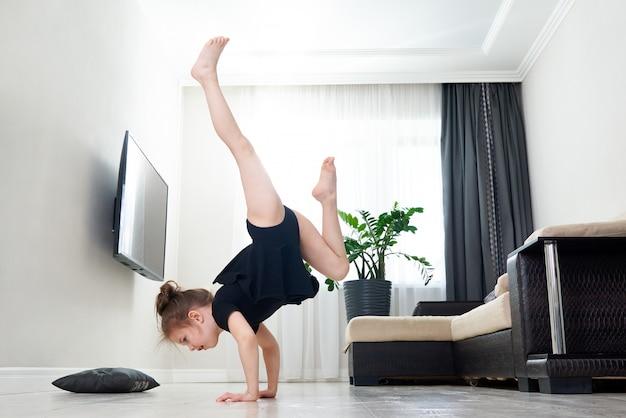 Маленькая девочка делает гимнастику дома стоя на руках вверх ногами