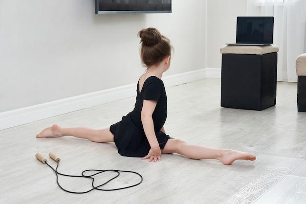 랩톱 컴퓨터, 인터넷 교육 개념으로 온라인 학습을 사용하여 집에서 체조 운동을하는 어린 소녀
