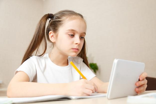 테이블에 집에서 숙제를 하 고 어린 소녀. 아이는 홈 스쿨링을합니다. 가벼운 머리카락을 가진 소녀는 노트북 및 태블릿 컴퓨터를 사용하여 온라인으로 작업을 수행합니다.