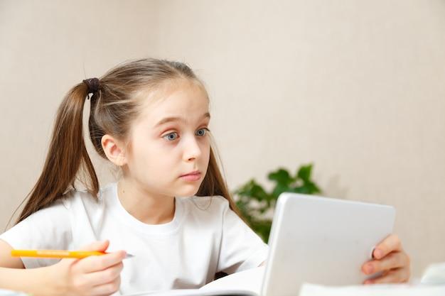 テーブルで家で宿題をしている女の子。子供は家庭教育を受けています。明るい髪の少女は、ラップトップおよびタブレットコンピューターを使用してオンラインでタスクを実行します。