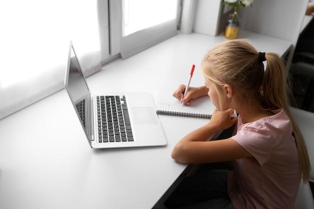 Маленькая девочка делает домашнее задание дома с ноутбуком и ноутбуком