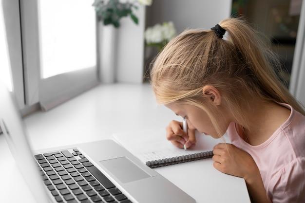 ノートパソコンとノートブックで自宅で宿題をしている少女