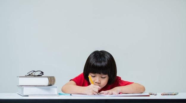 Little girl doing homework, kid writing paper on white wall, education concept