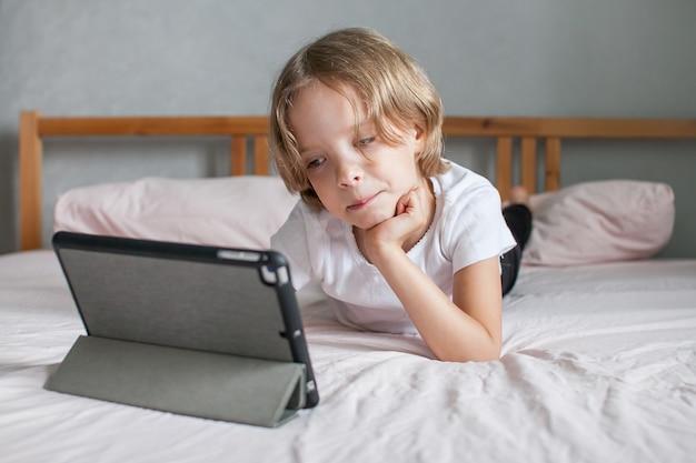 집에서 침대에 누워 온라인으로 숙제를 하는 어린 소녀. 온라인으로 친척과 의사 소통. 새 학년의 시작의 개념입니다. 고품질 사진