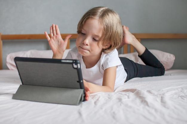 온라인으로 친척들과 집에서 침대에 누워 숙제를 하는 어린 소녀
