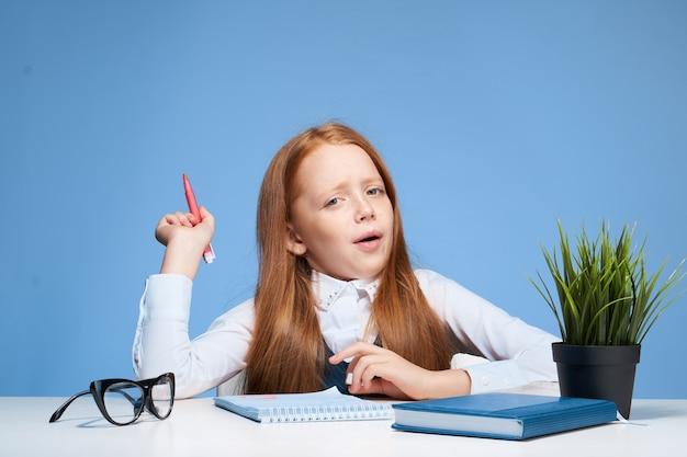 テーブルに座って宿題をしている少女