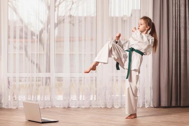 Little girl doing homework with taekwondo