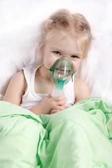 Little girl doing inhalation lying in bed