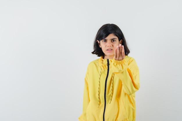黄色いパーカーの正面図で愚かな質問に不満を持って、イタリアのジェスチャーをしている少女。