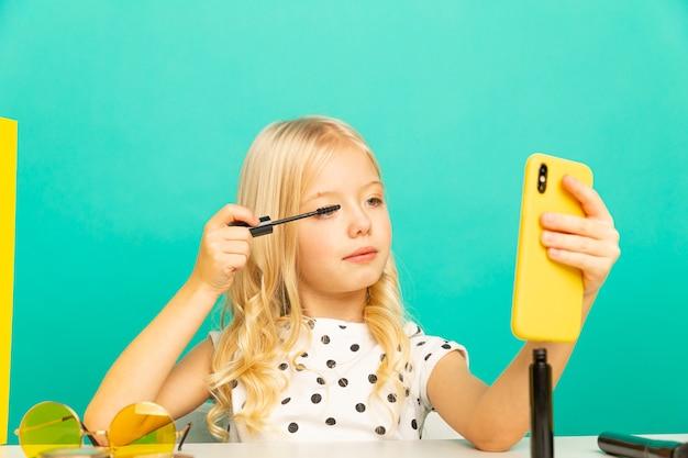 Маленькая девочка делает макияж на камеру для видеоблога. работаю блоггером, записываю видеоурок для интернета.