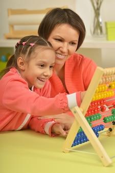 Маленькая девочка делает математические упражнения со своей матерью дома
