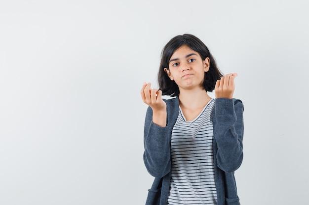 Маленькая девочка делает денежный жест в футболке, куртке и выглядит обеспокоенным.