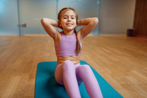 Маленькая девочка делает упражнения пресса на циновке в тренажерном зале, фитнес-тренировки. девушка в спортивной одежде, ребенок на тренировке в спортивном клубе