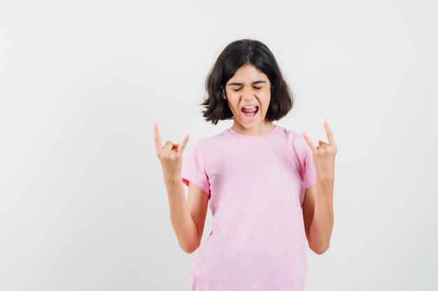 Маленькая девочка делает рок-символ, крича в розовой футболке и выглядит энергичным, вид спереди.